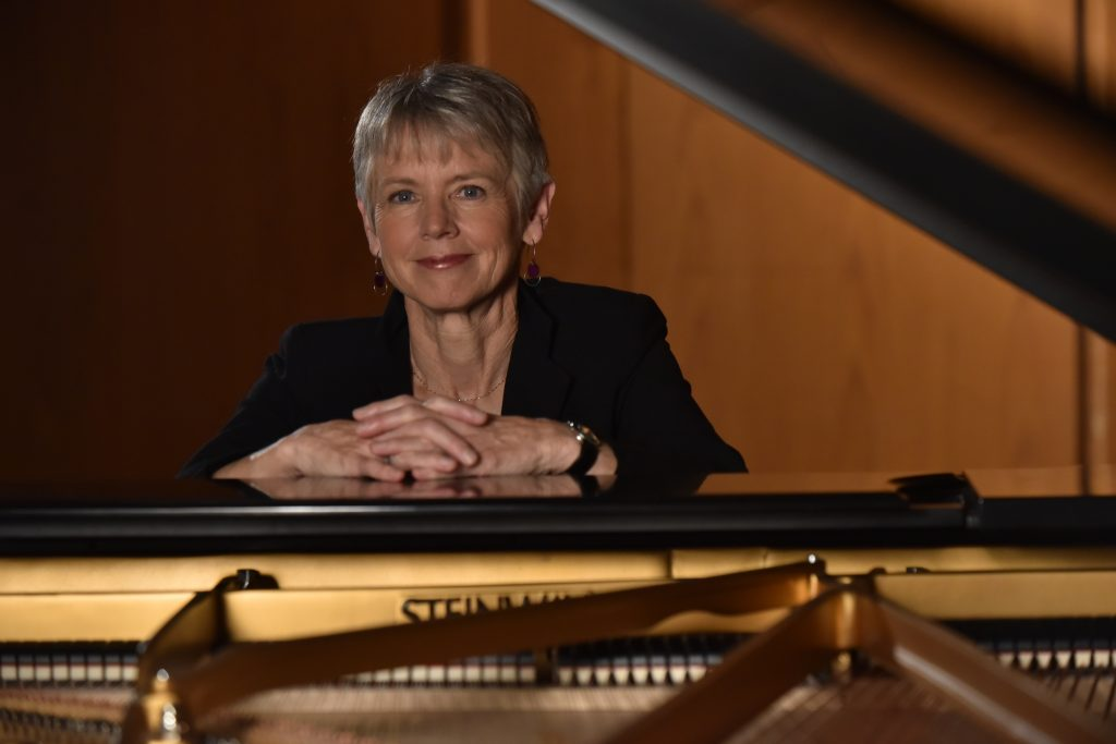 Ellen Rowe seated at a piano