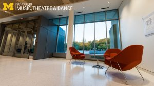 Zoom background, interior Brehm Pavilion lobby with bright windows and orange chairs