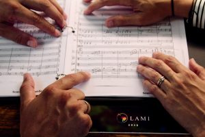 Maria and Regulo point to music notes on score