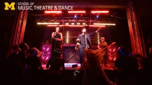 Zoom background - Musical Theatre performance of One Hit Wonder - showing a scene of a rock concert with singers, audience, and stage lights