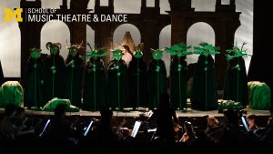 Zoom background - Opera chorus with performers holding Greek masks lit in green