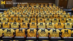 Zoom background - yellow SMTD shirts arrayed on seats in Britton Recital Hall
