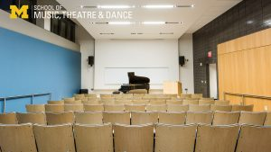 Zoom background - Watkins Lecture Hall, view of seats and piano from the rear of the room