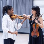 Danielle Belen teaching violin student in Hankinson Hall.