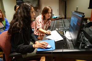Instructor and student at computer keyboard.
