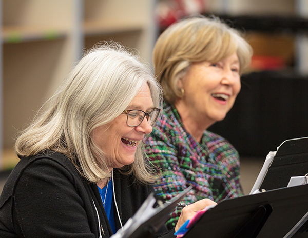 Two Voices Valiant chorus members laughing in rehearsal