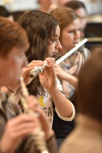 Three students playing the flutes