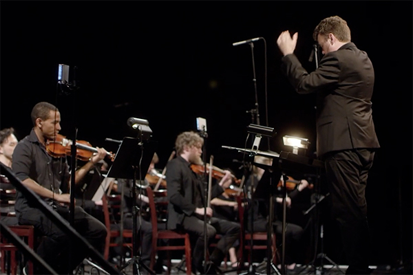 Professor Doug Perkins conducts 50 violinists at the Red Bull Music Festival