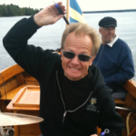 Mallet artist Anders Åstrand wearing sunglasses and a zip-up hoodie, sitting in a boat (assumed in Sweden), holding a stick or mallet in his right hand with arm raised above his head as if he is going to strike the camera with it. Facial expression is somewhere between a smile and a grimace. There is a boat captain, out of focus, sitting behind Anders in the boat.