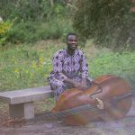 Daniel Kumapayi seated outside in front of the Moore pond with his bass.