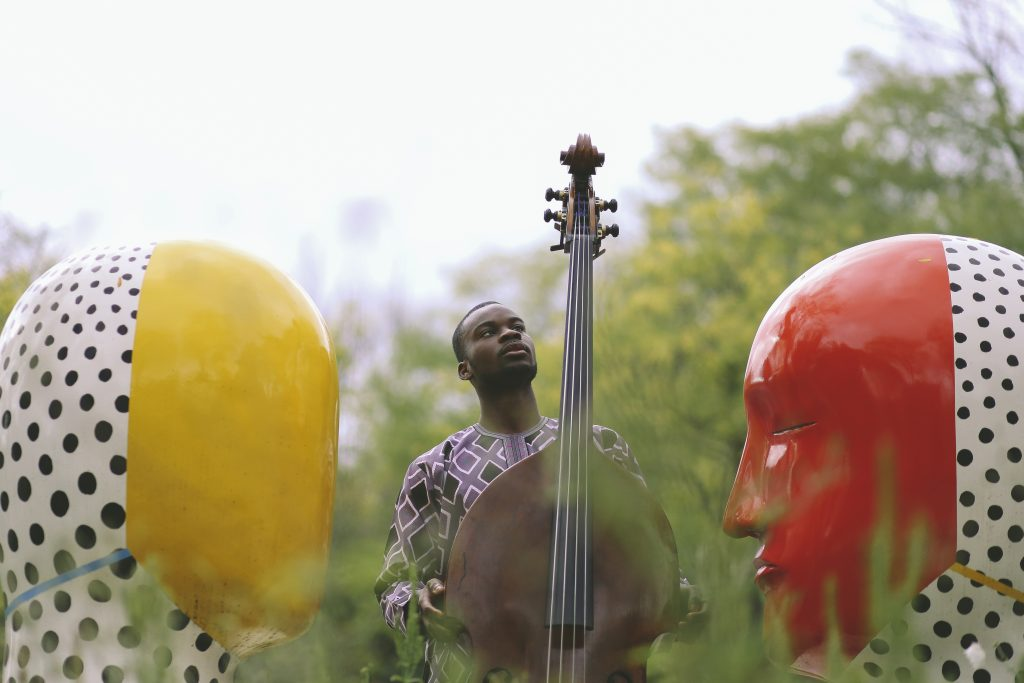 Daniel Kumapayi with his bass between the Moore head sculptures