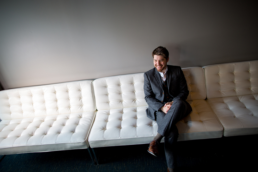 Composer Griffin Candey seated on a white couch