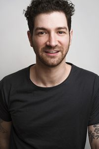 Adam Wachter wearing a black t-shirt and smiling at the camera.
