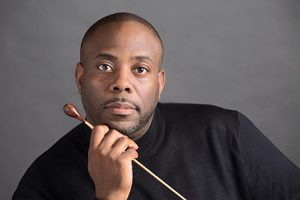 Damian Crutcher holding a baton under his chin, wearing a long-sleeved black shirt in front of a grey background.