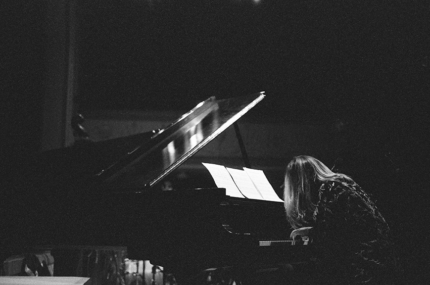 Taken from the back, a black and white photo of Sonya Belaya performing on an open grand piano. Her hair is obscuring her face and she is leaning in towards the keyboard.