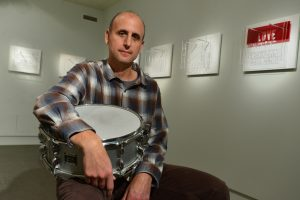 Michael Gould seated in an art gallery with a snare drum in his lap. He is surrounded by an installation of art he has created featuring acrylic cut outs of words on a white background.