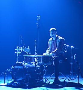 Michael Gould sitting at a drum kit bathed in blue light.
