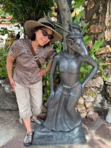 Christi-Anne Castro, wearing a sun hat, sunglasses, and brown and tan clothing, standing next to a statue in Bangkok. The statue is a dull metallic grey, slightly shorter than Christi-Anne.