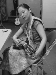 Black and white photo of Christi-Anne Castro in traditional Philippino dress, seated backstage, fixing a string on a banduria, a plucked instrument that is part of the rondalla.