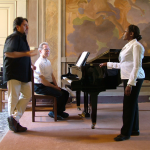 Prof. Timothy Cheek is seated at a piano while Leonardo De Lisi stands beside him instructing a female student.