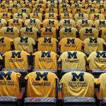 Yellow t-shirts with blue Michigan block m's and school of music, theatre, and dance written on them laying over chairs.