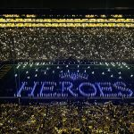 Still shot from the September 11 , 2021 Michigan Marching Band night-time half time show. The suite windows at the top of the stadium a lit yellow, below, the crowd, mostly wearing yellow shirts is highlighted, on the field, the Michigan Marching Band spells out HEROS in blue light (each band member has a light on their person).