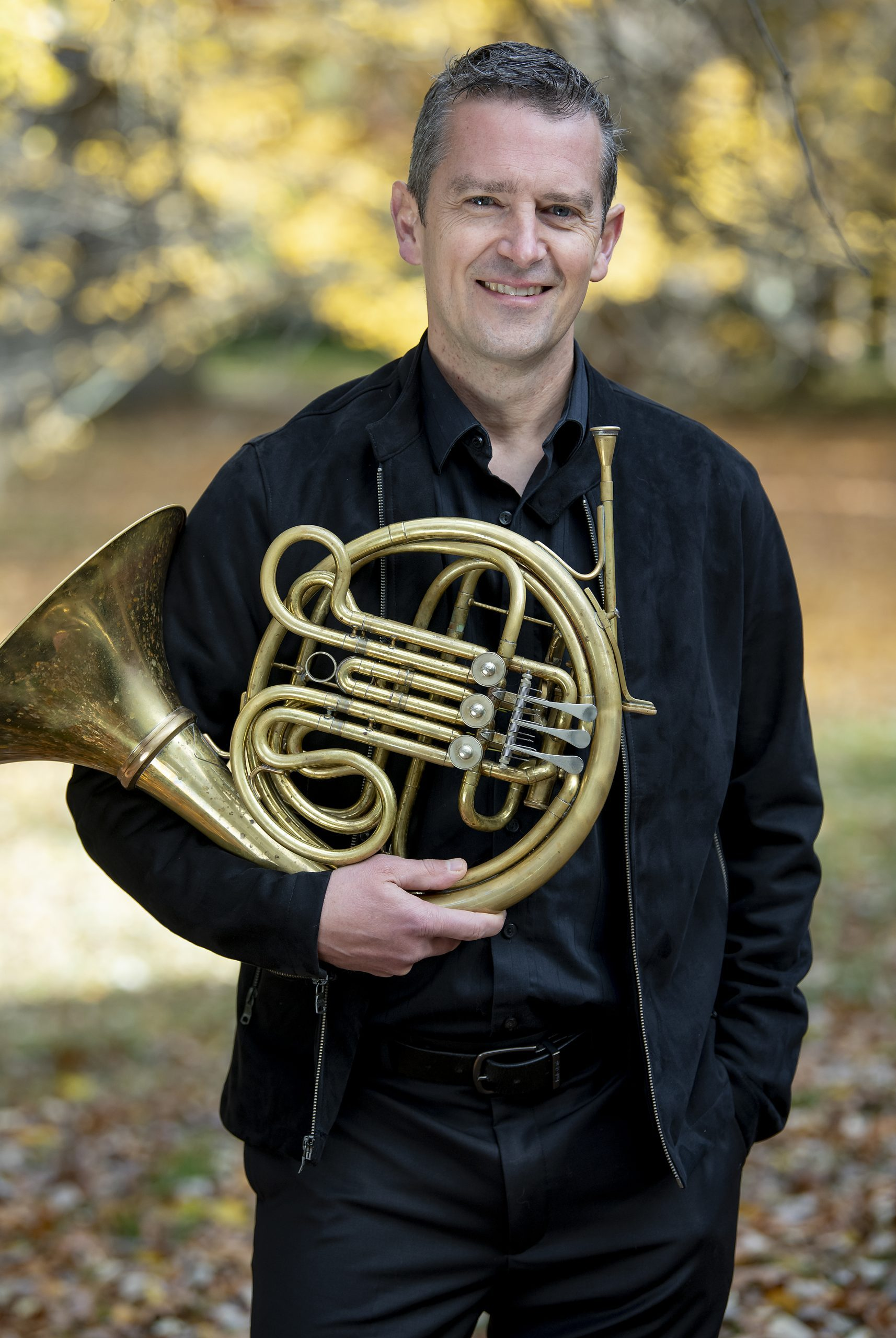 Adam Unsworth holding his horn in his right hand, smiling, in front of a blurred background of fall leaves.