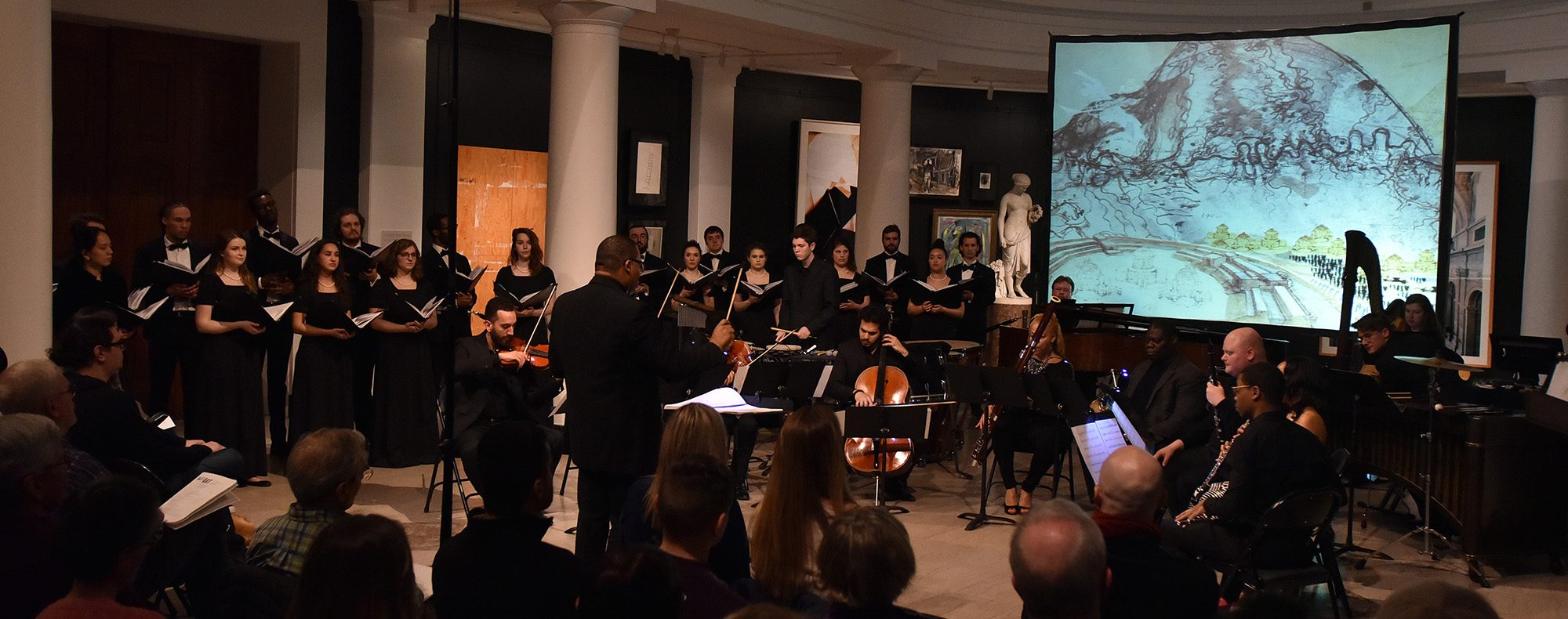 Chamber Choir in concert at the University of Michigan Museum of Art. Showing the choir, conducted by Professor Eugene Rogers in front of a screen depicting a painting from the collection.