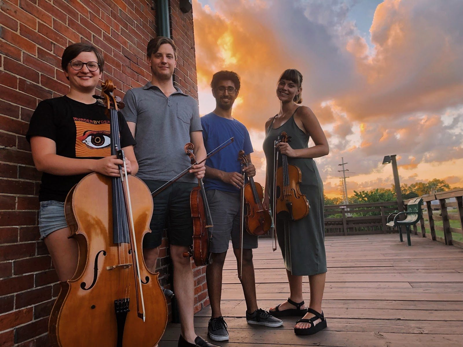 Converge Quartet -standing with their instruments in front of a sunset, left to right, Hanna Rumora, cello, Ryan McDonald, viola, Malhar Kute, violin, and Megan Rohrer, violin.