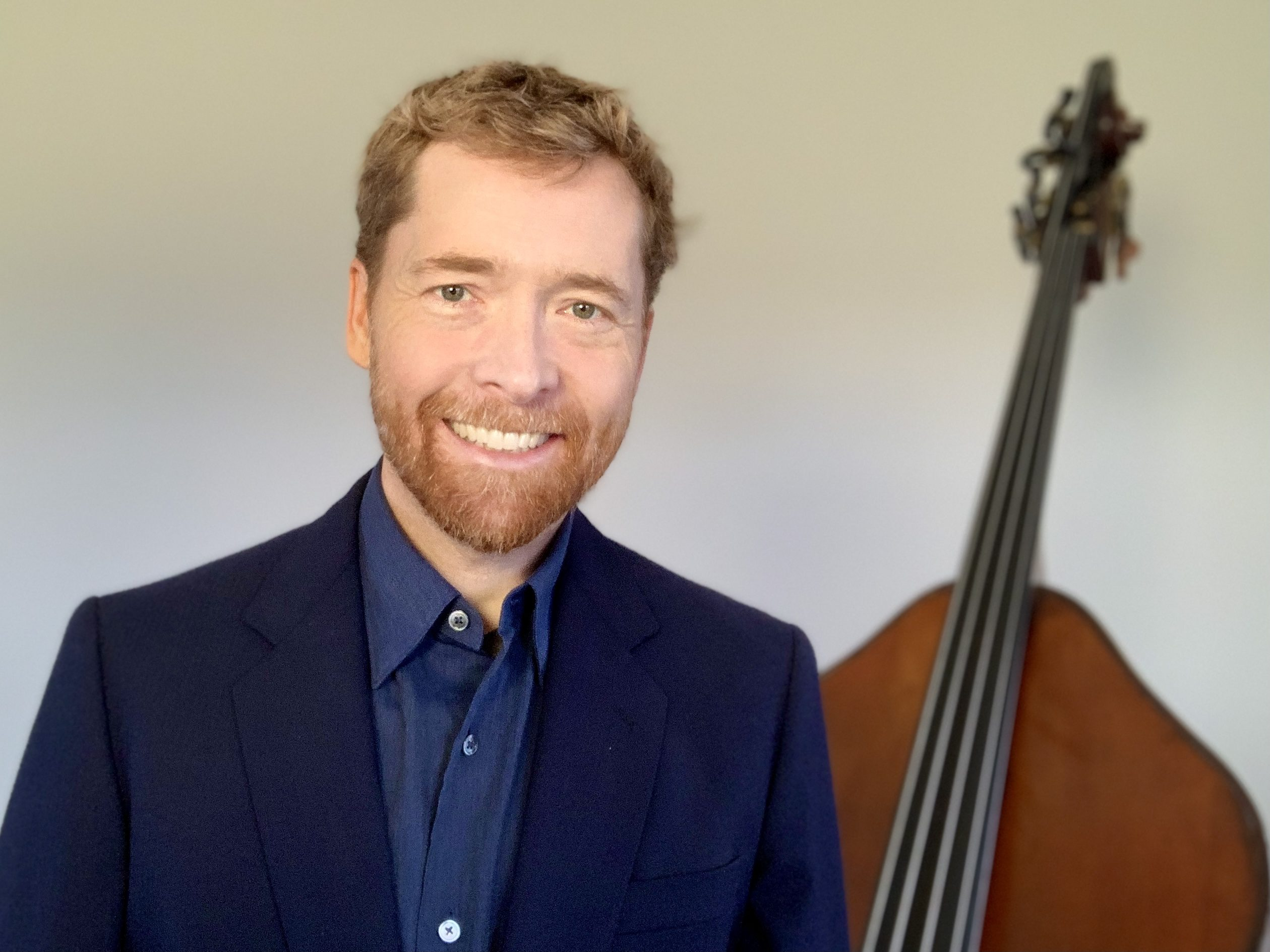 Nicholas Walker smiling with double bass in the background