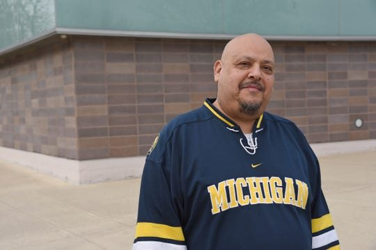 Jose Casas wearing a dark blue Michigan jersey with white and yellow stripes at the elbows, standing in front of the facade of the Arthur Miller Theatre.